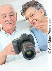 old couple relaxing at home using a camera