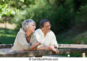 Old couple relaxing while standing on the bridge