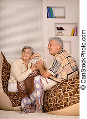 Old couple sitting at at armchairs