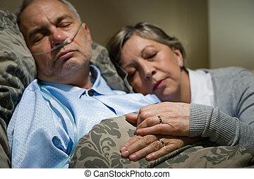 Old couple sleeping together man nasal cannula
