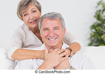 Old couple smiling at the camera and hugging in sitting room