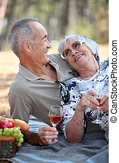 old couple taking a picnic beside trees