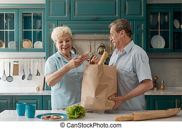 Old couple taking groceries out of a shopping bag