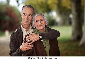 Old couple walking through park