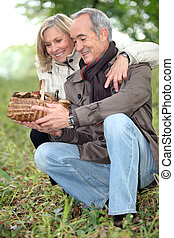 old couple watching a wickerwork basket of mushrooms in the ...