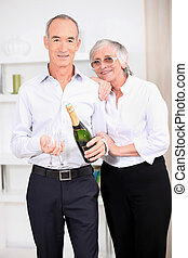Old couple with a bottle of champagne