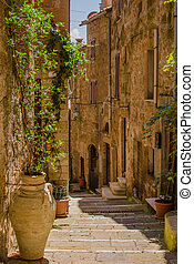 Old courtyard in Pitigliano with vases with flowers on the stairs