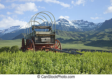 An old covered wagon sits in front of the Absaroka Mountains of Wyoming