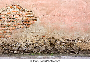 old cracked wall with a stone base - old cracked pink brick...