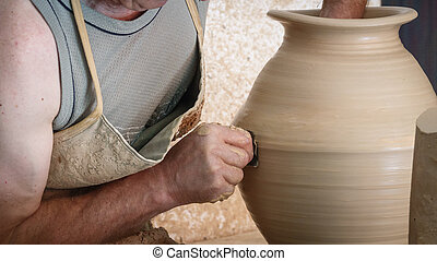 Old craftsman hands working on pottery wheel
