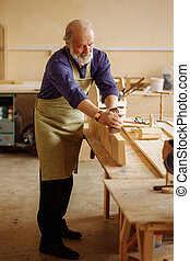 old craftsperson is working with building materials