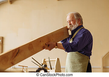 old craftsperson is working with timber indoors