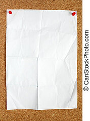 Old creased blank white paper attached to a cork noticeboard.
