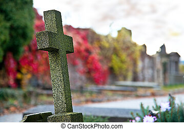 Old cross on graveyard in the autumn