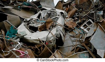 old crushed car is lying in heap of metal rubbish in a...
