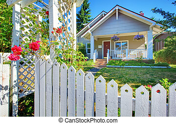 OLd cute grey house exterior behind white fence.