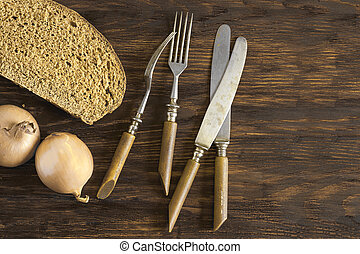 Old cutlery, a piece of rye bread and onions