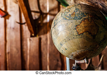 Old damaged globe against wooden wall.