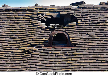 Old damaged tiled roof with a hole on the roof and broken tiles