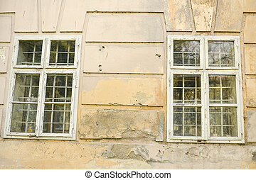 Old damaged wall of a castle with windows