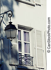 Old decorative lamp on a wall at a window