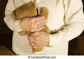 Old demented person is playing with bear