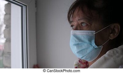 Old caucasian woman in protective medical mask looking sadly out window at street in cloudy weather, putting palm hand on glass, sitting at home in quarantine. Self isolation in coronavirus pandemic