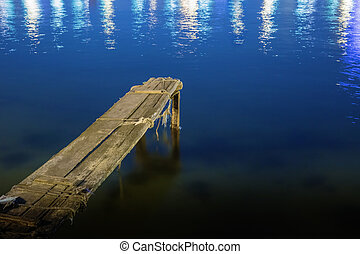 old dilapidated wooden pier at night