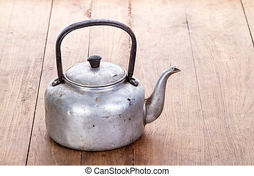 dirty classic aluminum kettle on wooden background