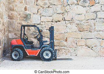 Old, dirty forklift in red on front of wall with copy space for text