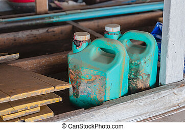 old dirty green plastic  oil gallon in garage
