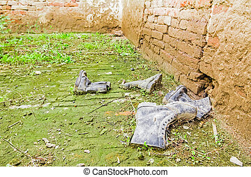 Old dirty shoes among grass and mud