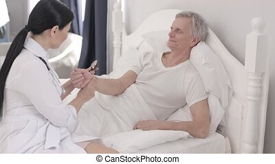Old disabled person in hospital - Young Nurse Checking Pulse...