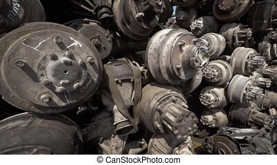 Old, Discarded Automotive Axles and Wheel Parts at the Junkyard