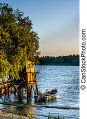 Old dock and the boat on the lake. Rustic landscape with wooden pier in the summer sunset