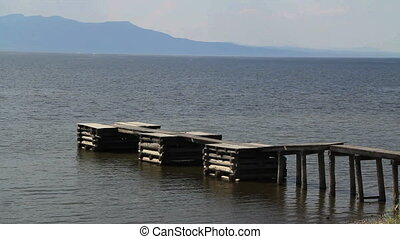 Old Dock - Old wooden dock stretches into water with misty...