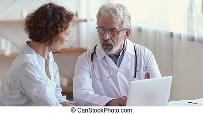 Old male doctor consulting female patient showing medical test results on laptop. Senior 60s physician explaining treatment talking to 30s woman client during checkup visit. Women healthcare concept.