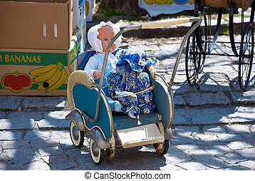 Old doll carriage with doll on the flea market
