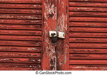 Old door red wood  peeling paint and key