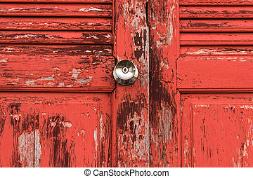 Old door red wood  peeling paint and knob