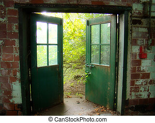 old doors - doors of an abandoned building open to lush, ...
