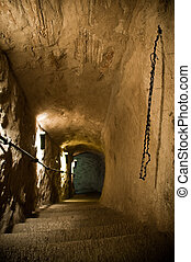 old castle tunnel with stairs leading down to dungeon