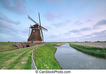 old Dutch windmill by canal, Groningen, Netherlands