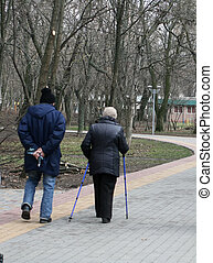Old elderly man and woman walking with a cane