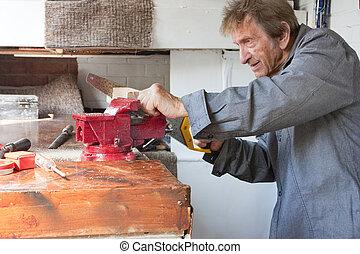 old elderly man sawing in workshop shed