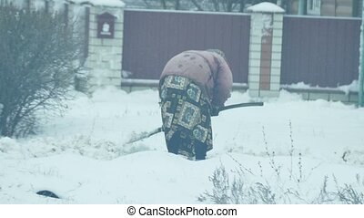 old elderly woman cleans snow pale winter