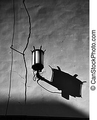 Old electric lamp with shadow on the wall, black and white