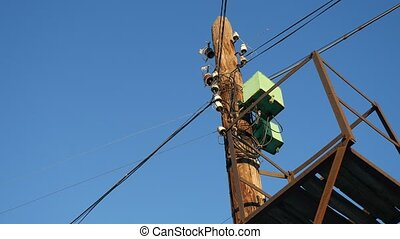 Old electric pole with wires on a background of blue sky -...