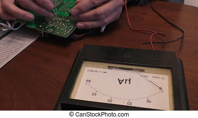Electronics engineer using old style retro ammeter meter for checking electric current in a circuit on a pcb for a fault