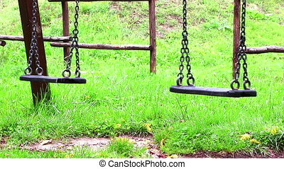 empty swings with chains swaying - old empty swings with...